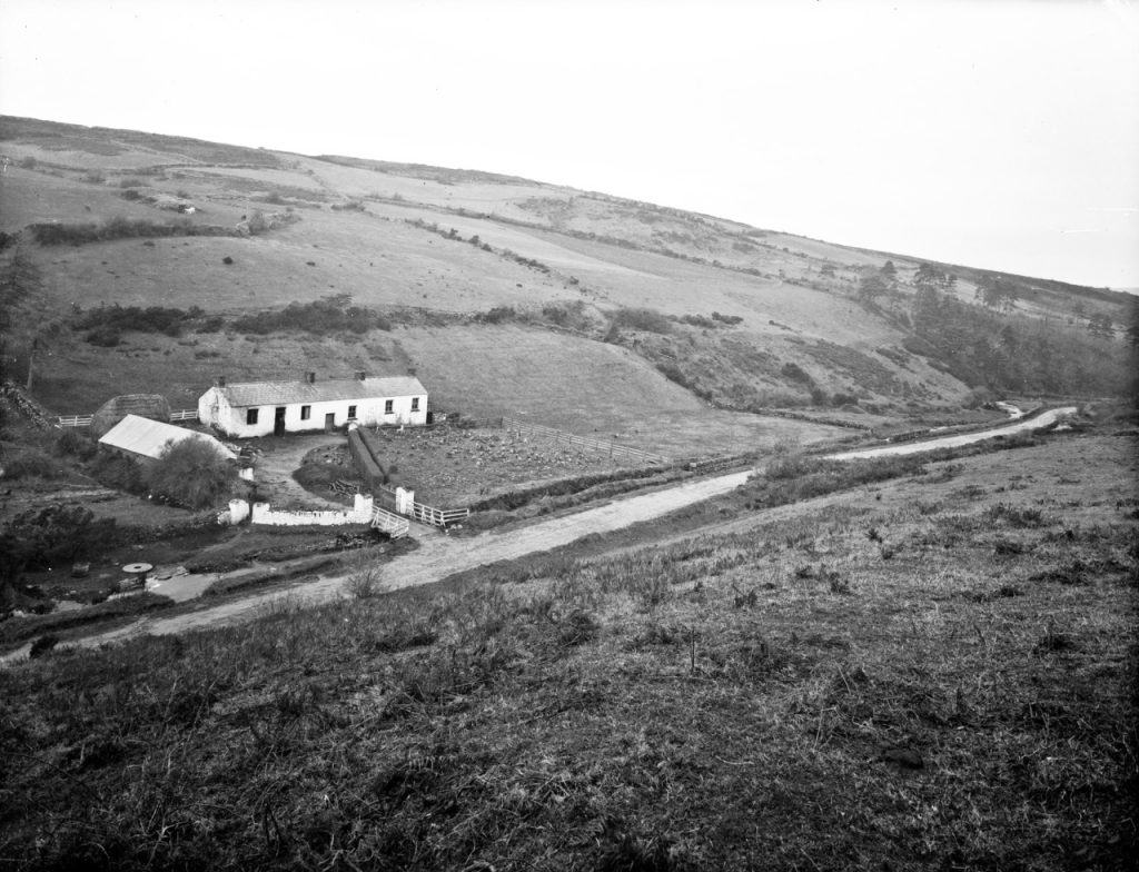 black and white picture of remote cottage on a hill