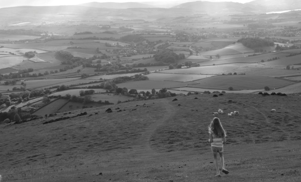 a black and white of a girl looking down over countryside