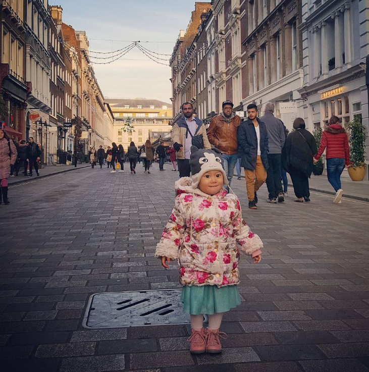 little girl on a busy high street in a blue skirt and pink tights boots and coat