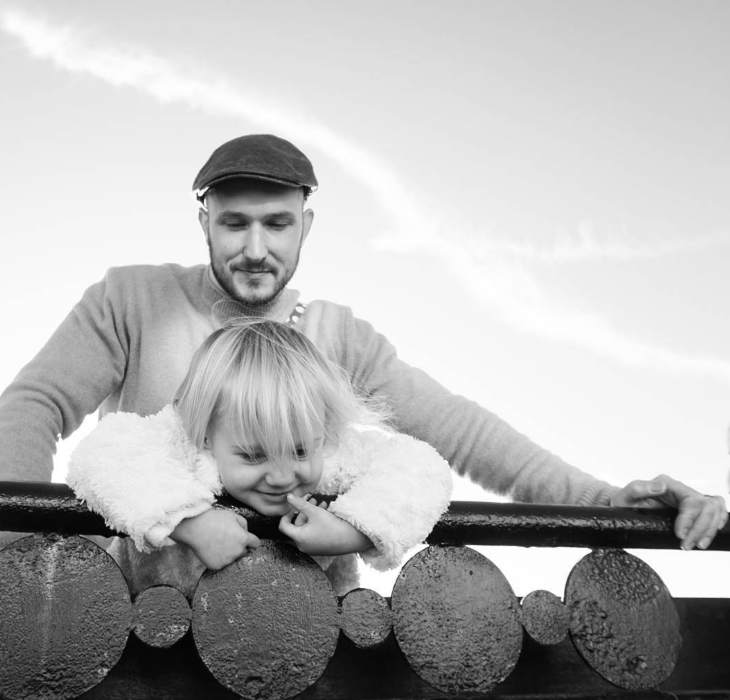 little blonde girl leaning over a wooden fence with her daddy above wearing a flat cap watching. picture in black and white