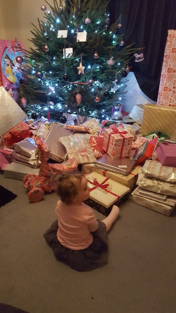 Alyssa sat in front of a lit chriistmas tree with all the presents in front of her