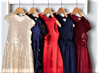 a rack of red gold and navy party dresses with sequins and bows