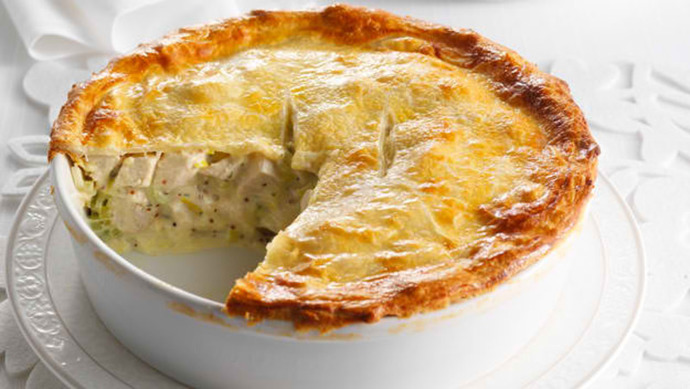 a chicken and mushroom pie with a segment missing in a white dish