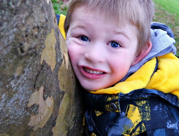 blonde little boy hugging a tree and smiling at the camera
