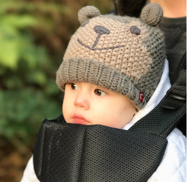 little baby in a body carrier in a white coat and a knitted bear hat with ears