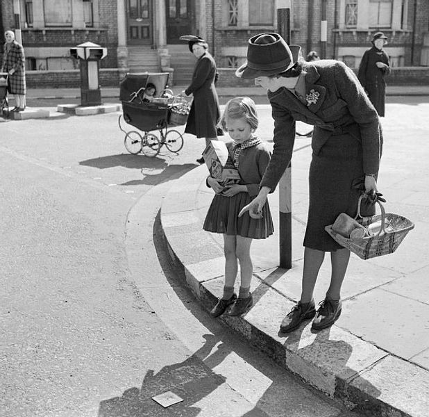 a mother teaching her child to cross the road safely - picture in black and white