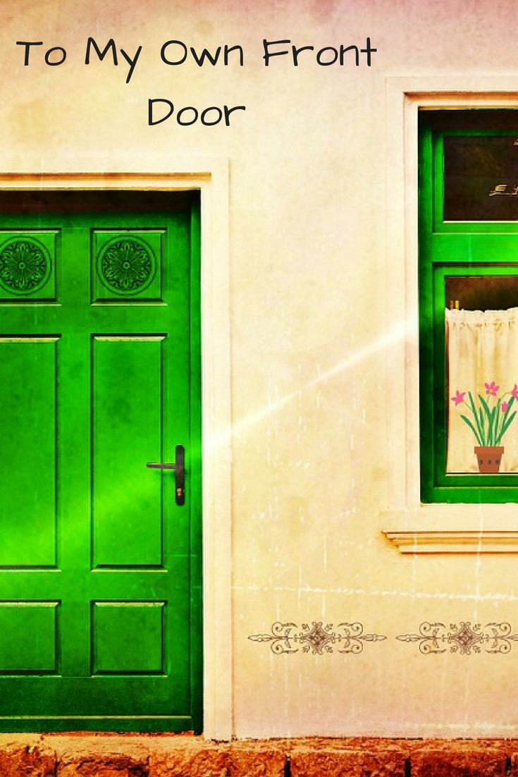a yellow wash building with a bright green front door and framed window with curtains