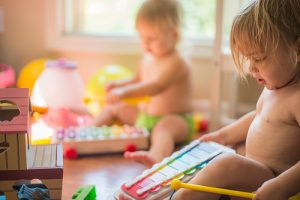 two children sat in nappies playing on musical instruments