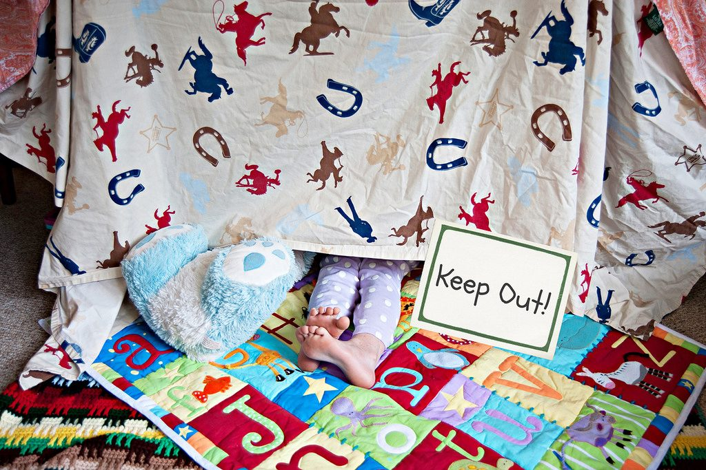 childs feet sticking out from underneath a piece of cowboy material with a sign saying keep out made into a den