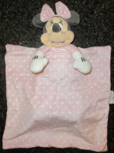 a minnie mouse toy with a pale pink bow attached to a pale pink and white spotty blanket - it is a child's comforter from Disney. She is called Mimmie