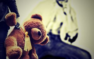 a brown teddy hanging from a childs hand with a yellow ribbon round his neck