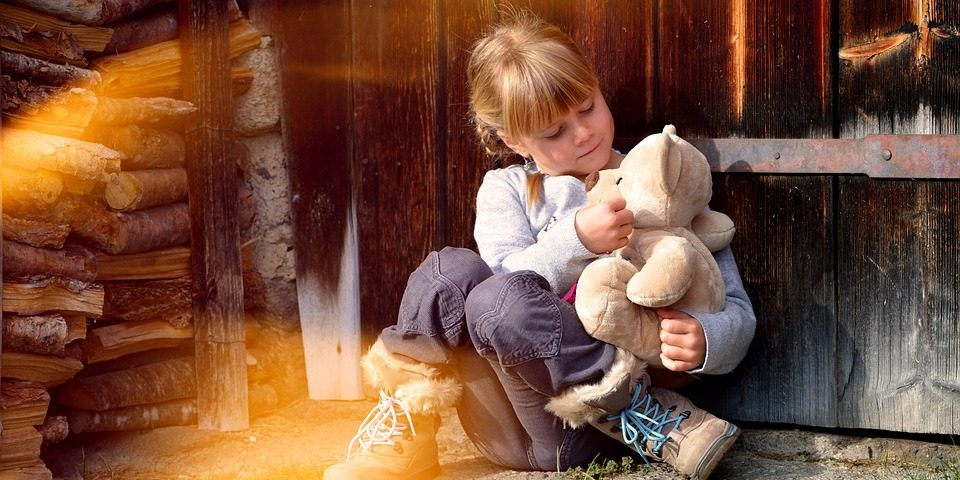 a little girl sat playing outside with her teddy against a wooden door on grass with sun shining down