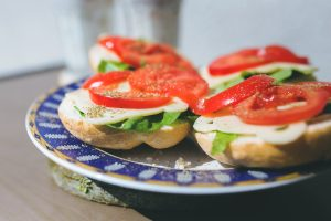 a plate with 4 open sandwiches with lettuce cheese and tomato on