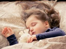a little brunette girl asleep on a bed with beige sheets in a navy tshirt cuddling a bunny