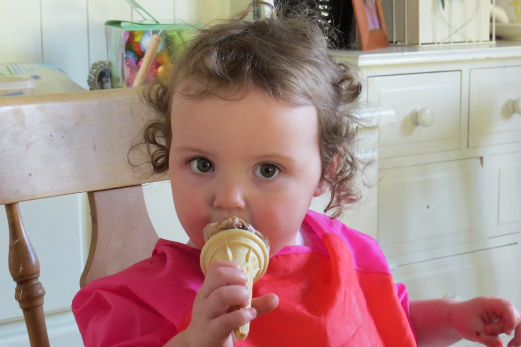 Alyssa in a red and pink apron eating a chocolate icecream cone with a beige sideboard behind her. she is looking at the camera