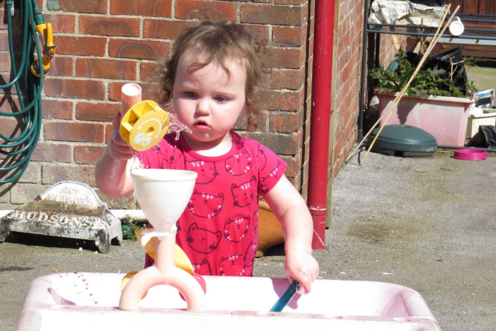 Alyssa in a pink t-shirt, in front of a brick wall playing at a water table with a funnel and a spoon