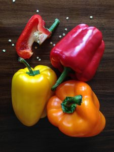 2 red peppers, 1 chopped and 1 yellow and 1 orange pepper on a wooden chopping board with seeds on it