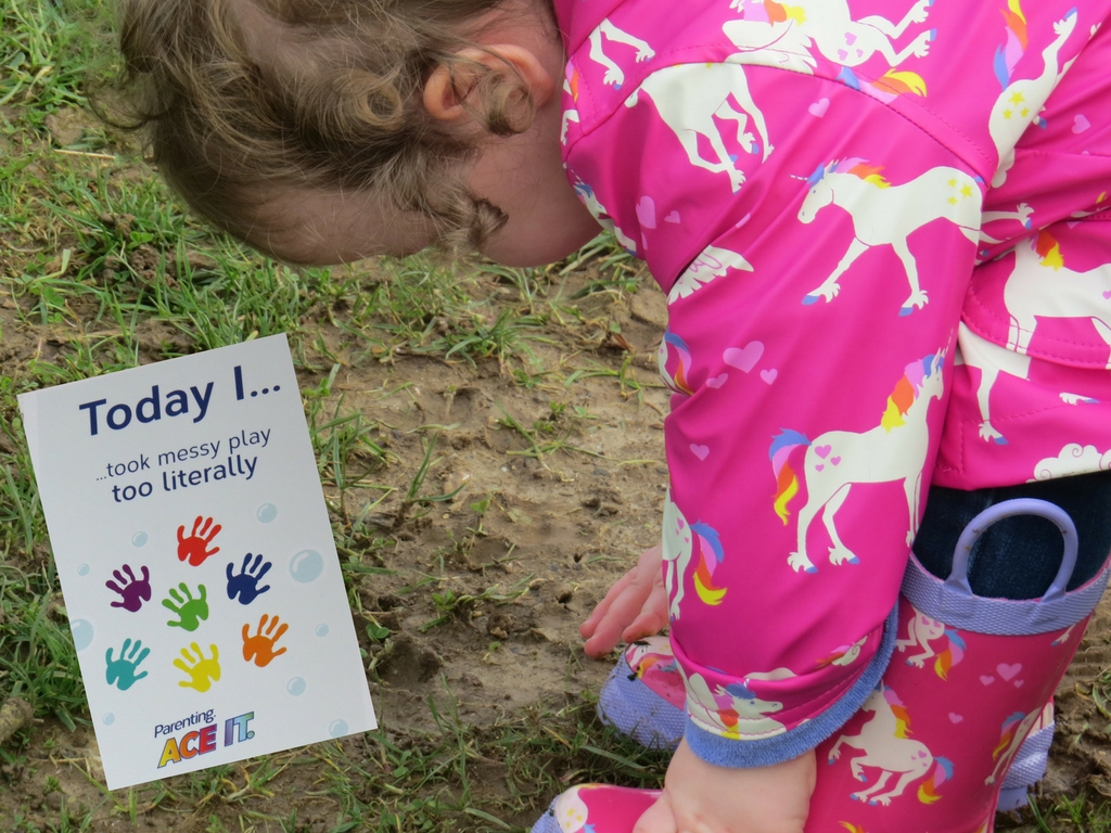 alyssa bending over to rub her hands in mud in her coat and wellies with a milestone card next to her saying that she has taken messy play to the next level