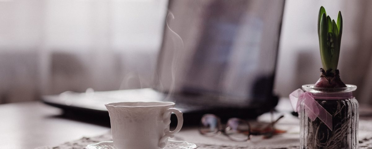 a laptop in the background open on a table. in front of it on a doily is a steaming cup of coffee in a white cup and saucer