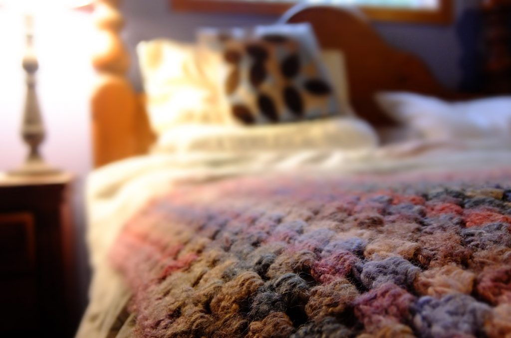 a crochet knit multi coloured blanket on a bed with a pillow and the bed head blurred in the background with a lamp to the left