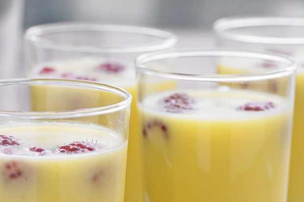 4 glass jars with yellow coloured pudding inside with raspberries buried inside
