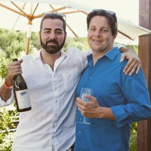 two men arms round each other smiling at camera holding a glass and a bottle of wine
