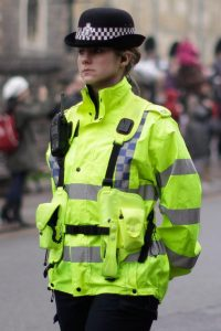 police woman with a yellow high visibility jacket on and a black police hat on standing in the street