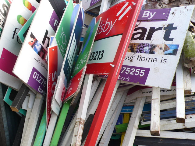 a collection of different for sale signs all stacked together