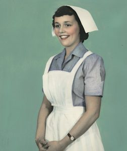 an old picture of an old fashioned nurse in uniform smiling at the camera