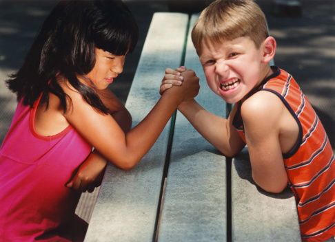 dark haired girl in pink top and fair haired boy in orange top gritting teeth and arm wrestling. boy looking at camera
