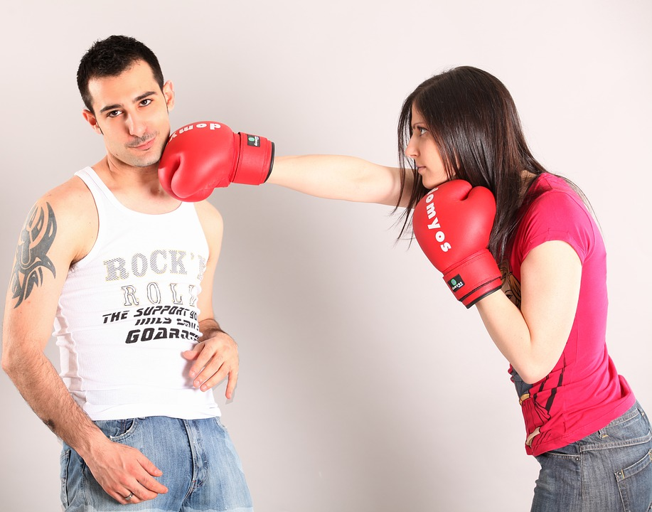 a woman wearing boxing gloves punching a man looking at the camera in the face