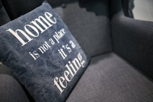 "blue cushion on a grey chair with white writing on saying ""home is not a place it's a feeling"""