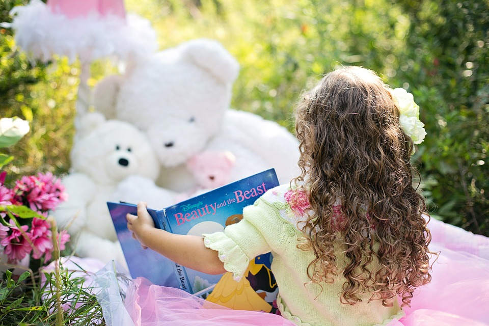 little girl back to camera with curly hair reading a book to teddy bears outside