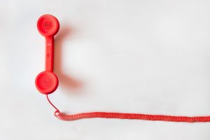 white background with a red long cord telephone