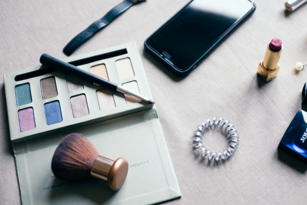 flat lay on white wood of makeup and a phone