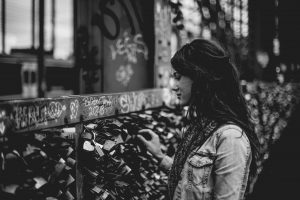 a brunette woman in a jacket with long hair in front of a graffitied wall that is covered in locks. she is touching one