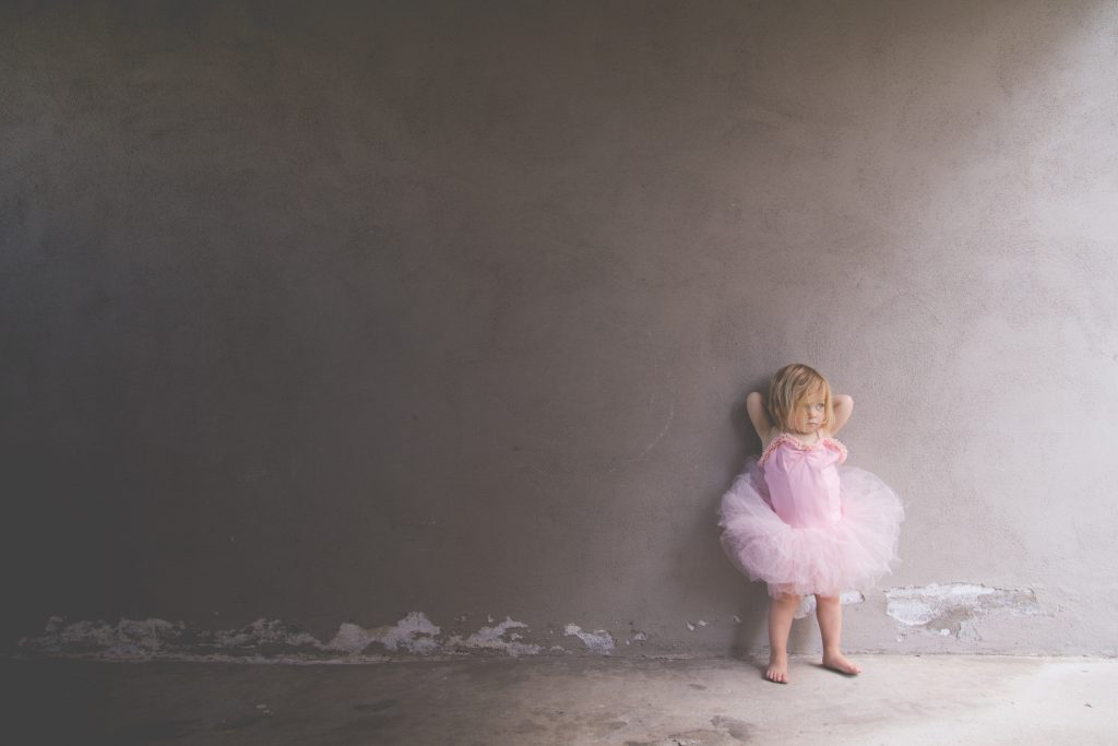 little blonde toddler leaningagainst a grey wall with her hands behind her head wearing a pink tutu
