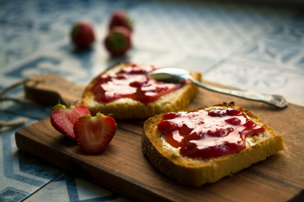 two slices of toast on a chopping board with a knife and strawberry jam on them and a strawberry cut in half on the board