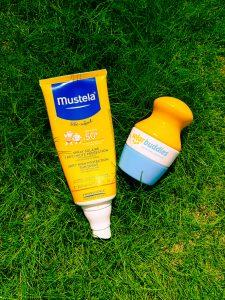 a yellow and blue tube of Mustela suncream next to a yellow white and blue plastic solar buddies suncream applicator both on green grass