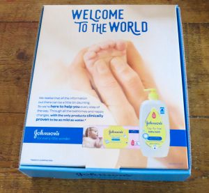 a johnsons box with a mums hand holding a baby's foot with the top toe toe bottles and logo pictured below all on a wooden table