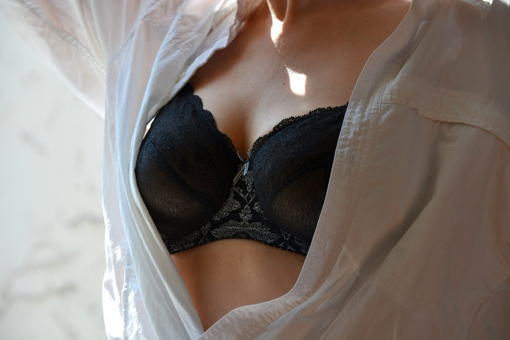 a woman's chest wearing a black lace bra underneath an open white shirt
