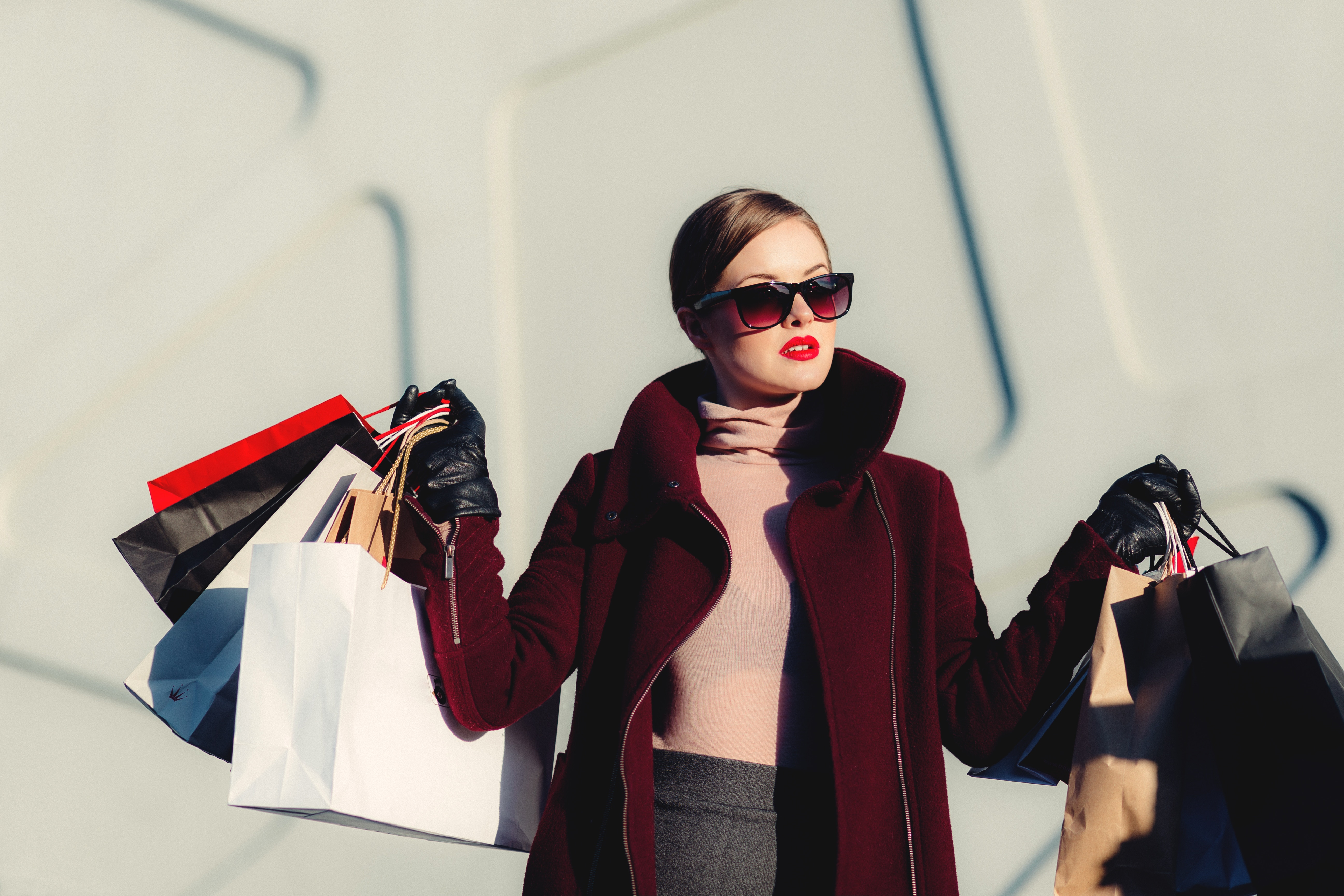 a woman in a red coat and sunglasses in front of a white building holding up lots of shopping bags in both hands