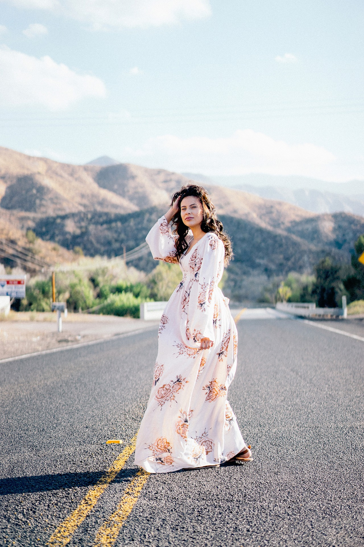 a woman wearing a white and floal maxi dress standing in the middle of a deserted mountain road pushing her brown hair out of her face