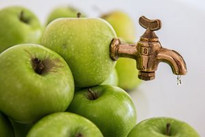 a pile of green apples on a white background. one on the top has a gold tap sticking out of it. it's turned off