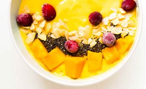 a white bowl with a yellow smoothie inside topped with fruits and nuts