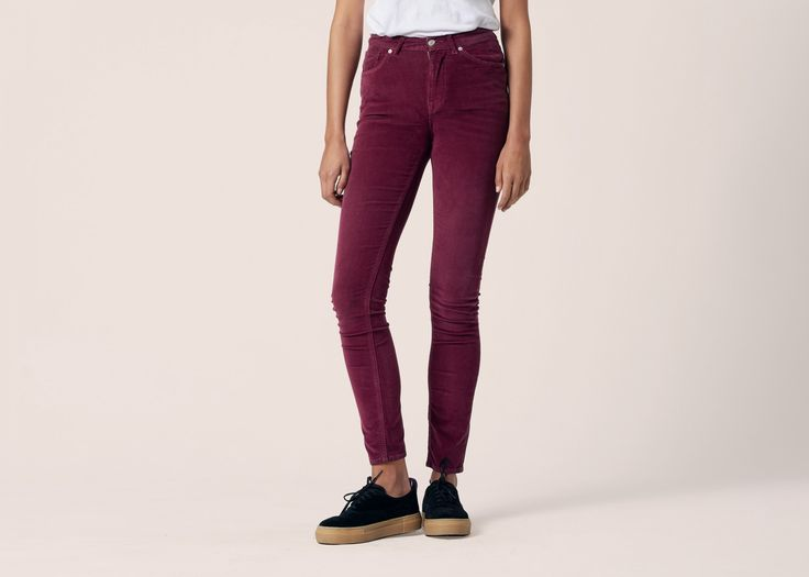a woman's legs wearing red corduroy trousers and sneakers on a plain blush pink background