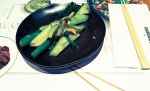 fried broccoli and pak choy on a black plate next to chopsticks