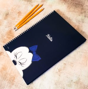 a navy blue minnie mouse a4 notepad with minnie mouse on the front and 3 orange pencils next to it
