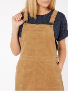 woman wearing a mustard yellow corduroy dress with a blue tshirt underneath. you cant see her face but she has blonde hair