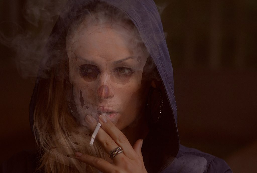 a woman in a blue hoodie with a cigarette to her mouth, smoke all around her and half her face appearing skull like